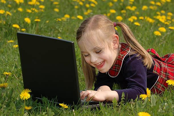 Lächelnd Mädchen auf Wiese mit laptop – Foto