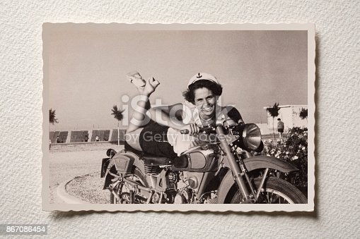 Old photograph of a smiling girl on motorbike