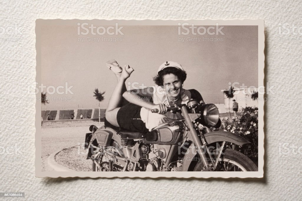 Smiling girl on motorbike at the sea. Photograph of the 50s. stock photo