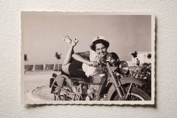 smiling girl on motorbike at the sea. photograph of the 50s. - old fashioned stock pictures, royalty-free photos & images