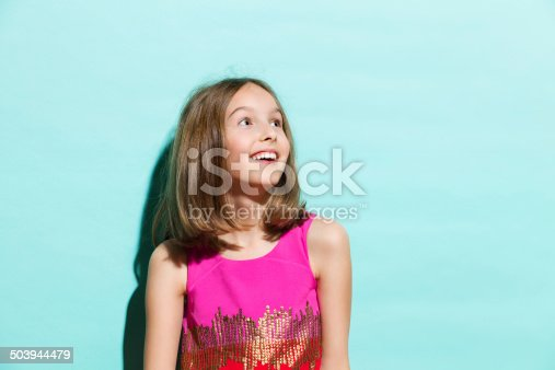 istock Smiling girl on turquoise background looking up 503944479