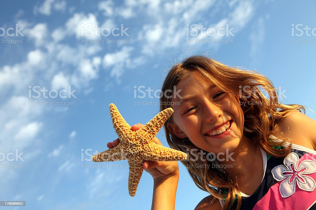 Smiling Girl on Vacation holding Starfish royalty-free stock photo
