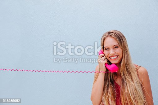 istock Smiling girl on vintage telephone 513585952