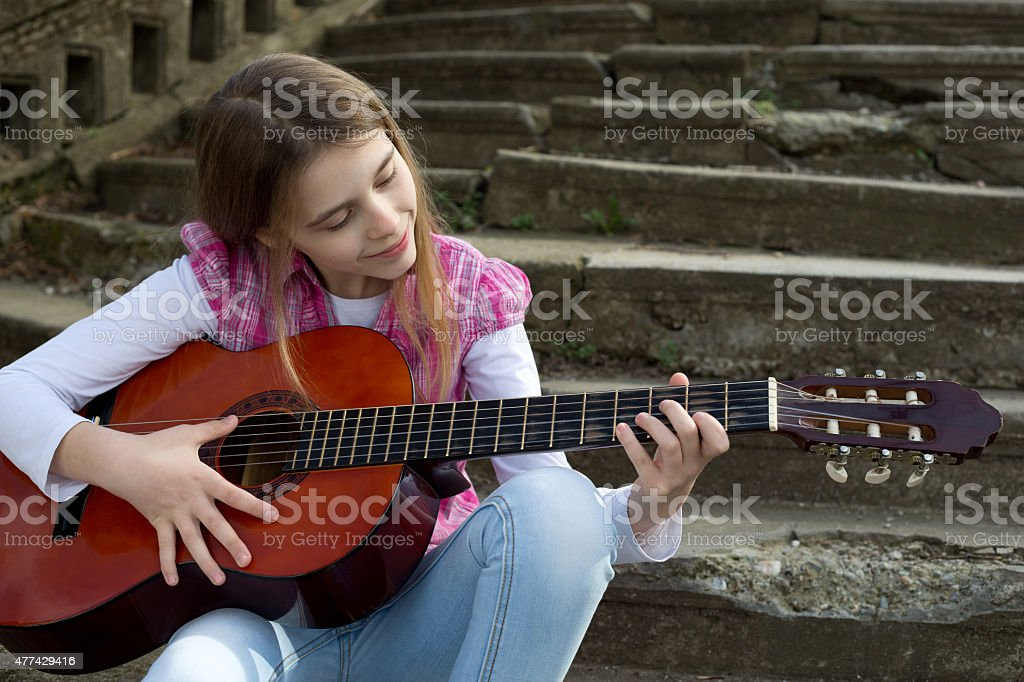 Smiling Girl Playing a Guitar Against Old Stone Staircase stock photo