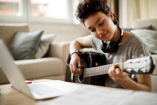 smiling girl playing a guitar at home - music foto e immagini stock