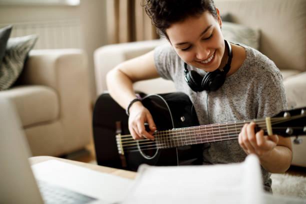 Lächelndes Mädchen spielen einer Gitarre zu Hause – Foto