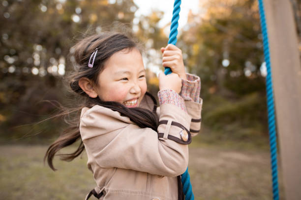 Smiling girl playing in autumn park stock photo