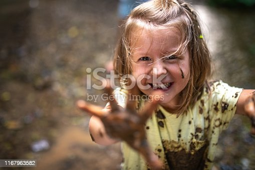 Portrait of smiling girl playing with mud in forest.