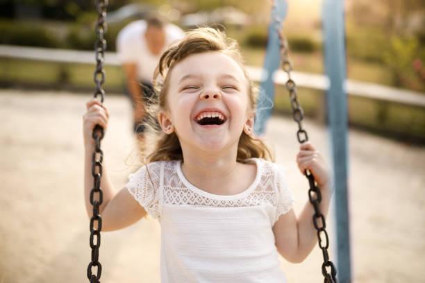 ragazza sorridente che gioca sull'altalena - bambino foto e immagini stock