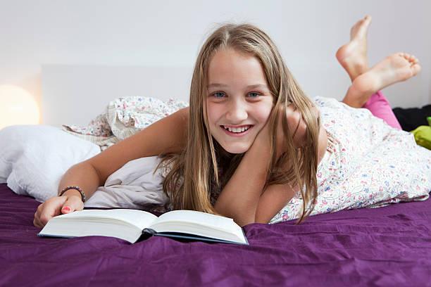 Lächelnd Mädchen lesen im Bett – Foto
