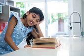 smiling girl reading novel at kitchen counter