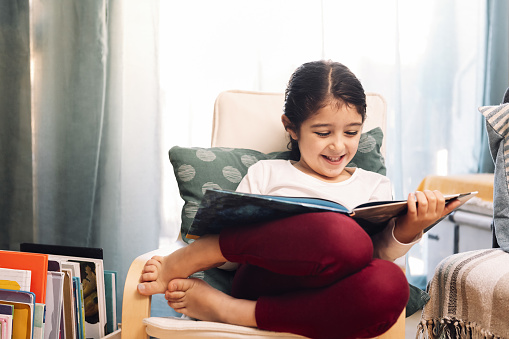 smiling little girl reading sitting at home, concept of leisure at home for children
