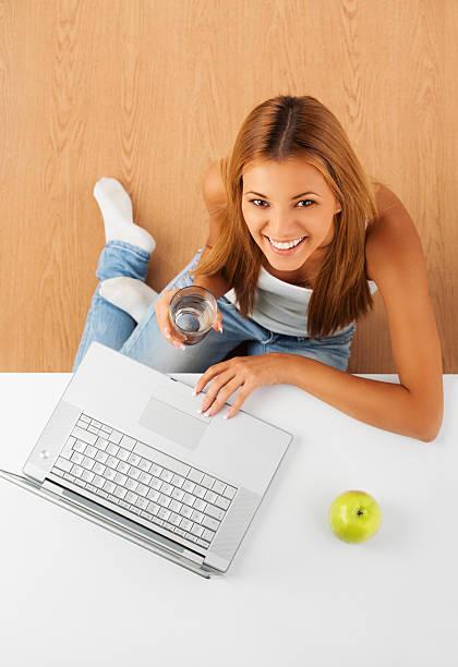 lächelnde frau entspannung zu hause mit laptop-computer. - marko skrbic stock-fotos und bilder