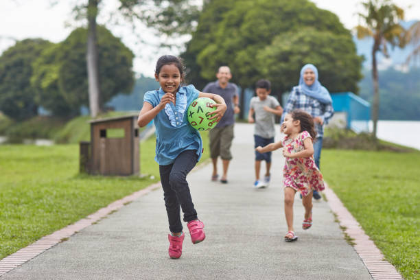 Smiling girl running with ball against family stock photo