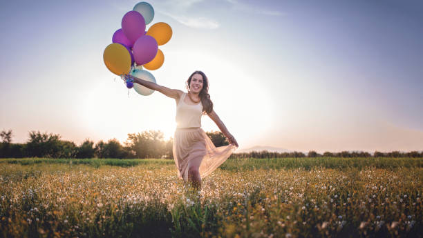 smiling girl running with balloons - mulher balões imagens e fotografias de stock