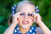 Smiling girl showing blueberries in front of her face - covering her eyes with blueberries