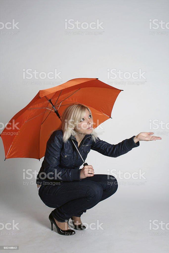 Smiling girl siting under umbrella royalty-free stock photo