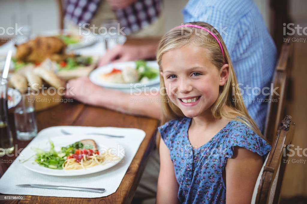 Yemek masada oturan gülümseyen kız royalty-free stock photo