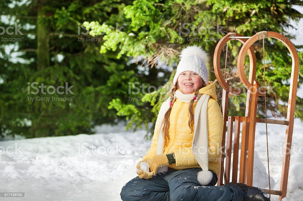 Smiling girl sitting in forest after sledging stock photo