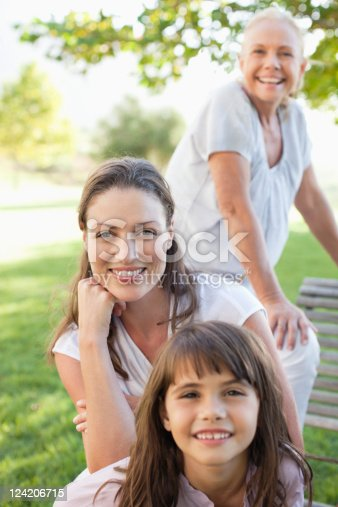 istock Smiling girl sitting in park with mother, grandmother in background 124206715