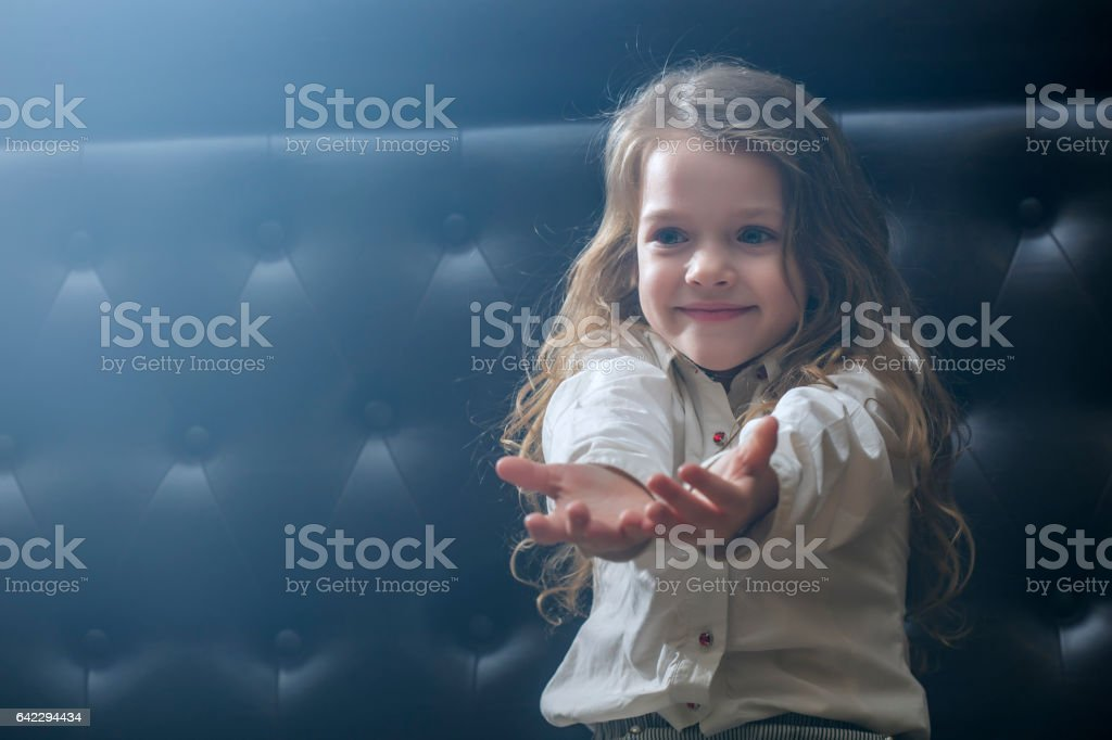 Smiling girl sitting on couch reaching her hands out stock photo