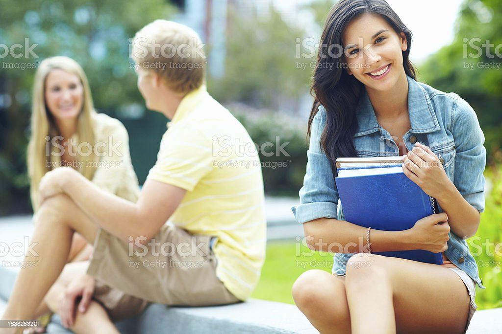 Smiling girl sitting outdoors holding books royalty-free stock photo