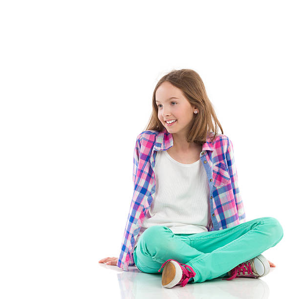 smiling girl sitting with legs crossed - sitting on floor stock photos and pictures