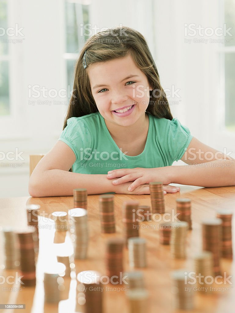 Smiling girl sitting with stacks of coins royalty-free stock photo