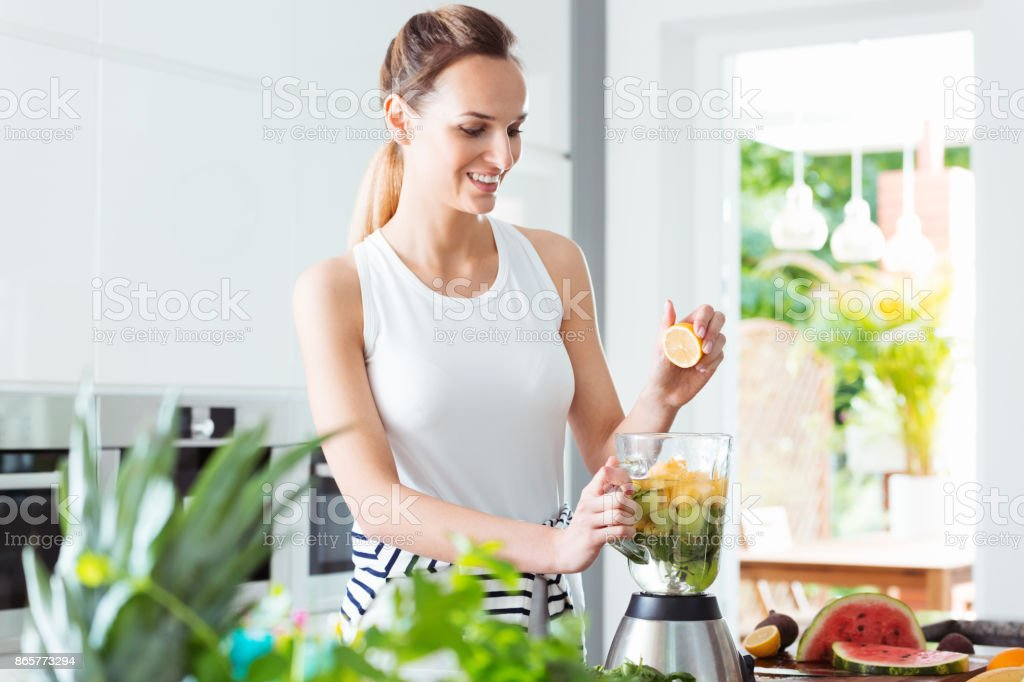 Smiling girl squeezing fruit juice stock photo