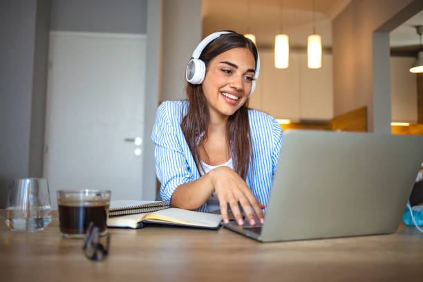 Smiling girl student wear wireless headphone study online with skype teacher Smiling girl student wear wireless headphone study online with skype teacher, happy young woman learn language listen lecture watch webinar write notes look at laptop sit in cafe, distant education video call stock pictures, royalty-free photos & images