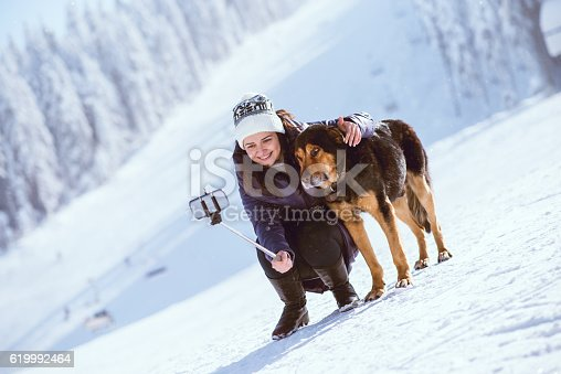 istock Smiling Girl Taking Selfie with Her Dog at Snowy Mountains 619992464