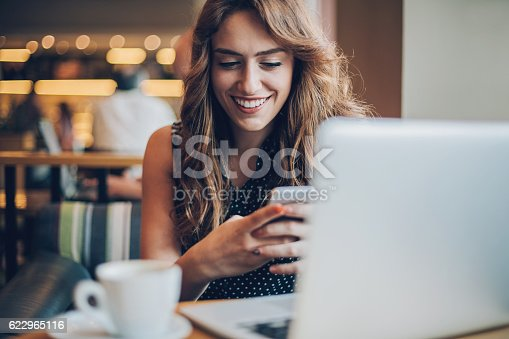 istock Smiling girl texting in cafe 622965116