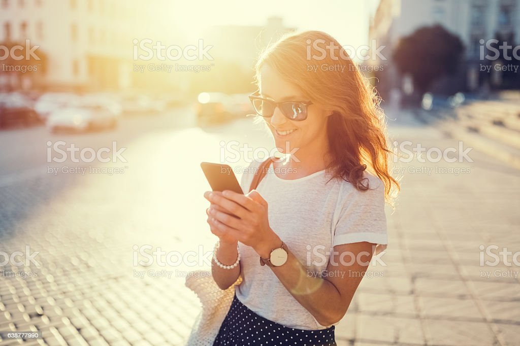 Smiling girl texting outside stock photo