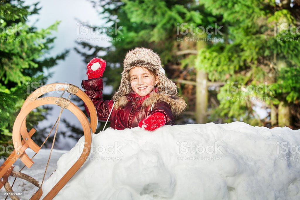 Smiling girl throwing snowball from the snow tower stock photo