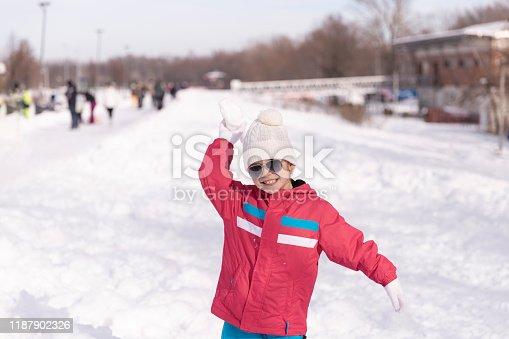 istock Smiling girl throwing snowball 1187902326