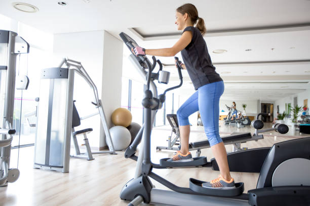 Smiling Girl Training on Stair Stepper in Gym stock photo