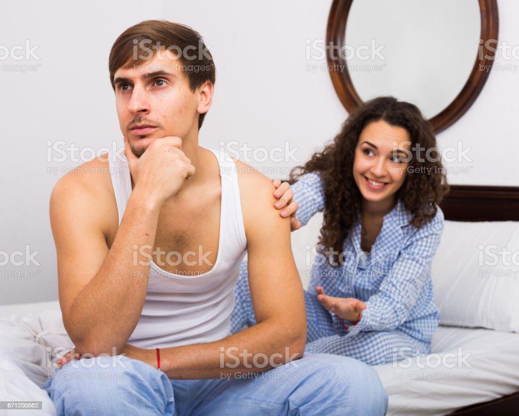 Smiling girl trying to comfort upset husband stock photo