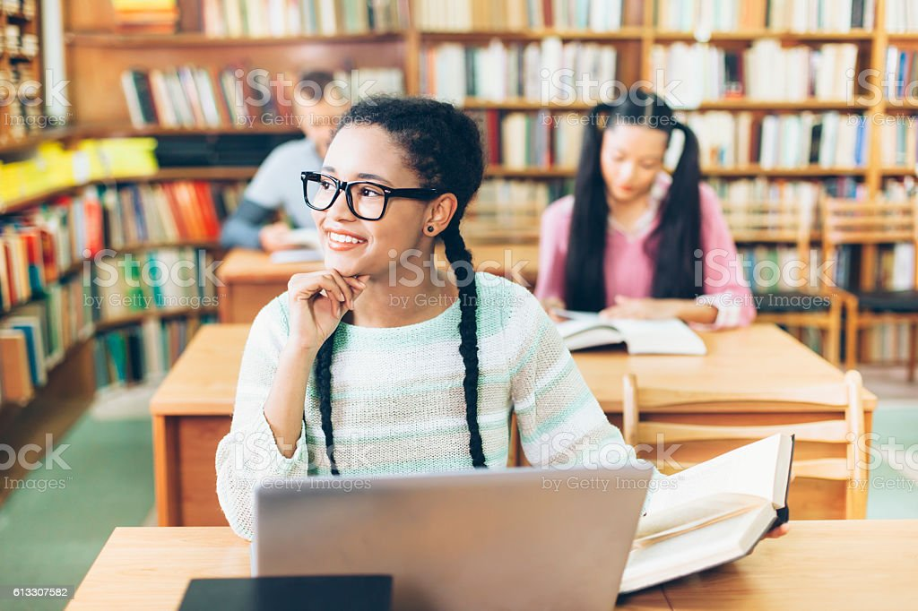 Smiling girl using laptop at library stock photo