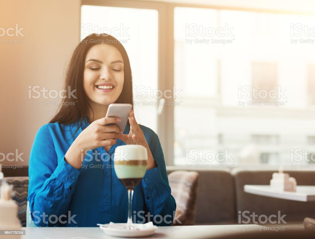 Smiling girl using smartphone to take photo of cocktail royalty-free stock photo
