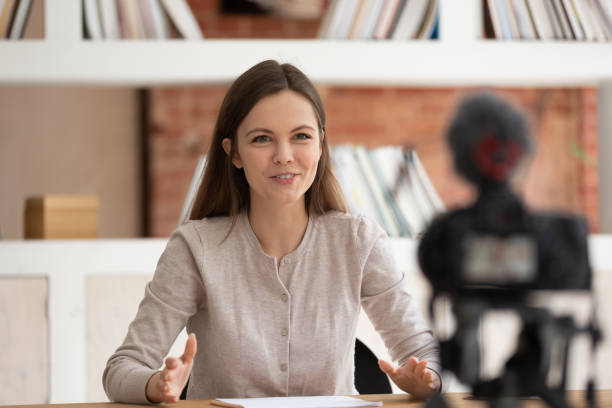 smiling girl vlogger record talk video on professional camera - dodatkowa praca zdjęcia i obrazy z banku zdjęć