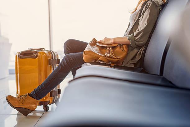 smiling girl waiting for boarding - donna valigia solitudine foto e immagini stock
