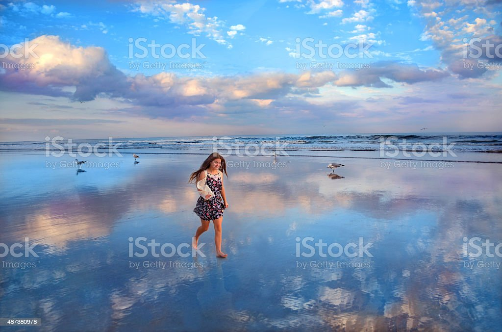 Smiling girl walking on beautiful beach. stock photo