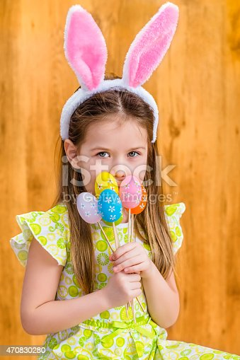 istock Smiling girl wearing bunny ears, holding bunch of colorful eggs 470830280