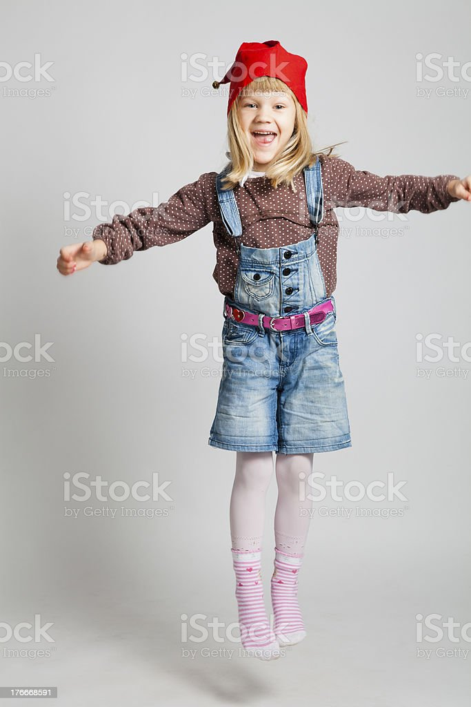Smiling girl wearing Christmas hat and jumping royalty-free stock photo