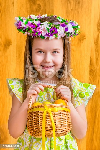 istock Smiling girl wearing floral wreath, holding basket with yellow eggs 470830028