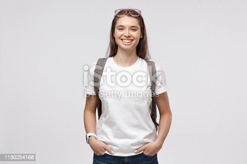 Smiling girl wearing white t-shirt and backpack, isolated on gray background
