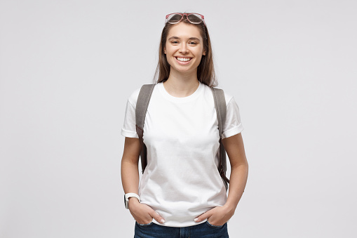 istock Smiling girl wearing white t-shirt and backpack, isolated on gray background 1150254168