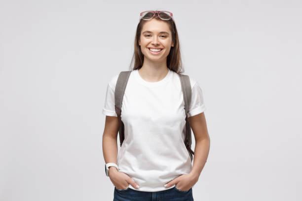 흰색 티셔츠와 배낭을 입고 웃는 소녀, 회색 배경에 고립 - 백인종 뉴스 사진 이미지