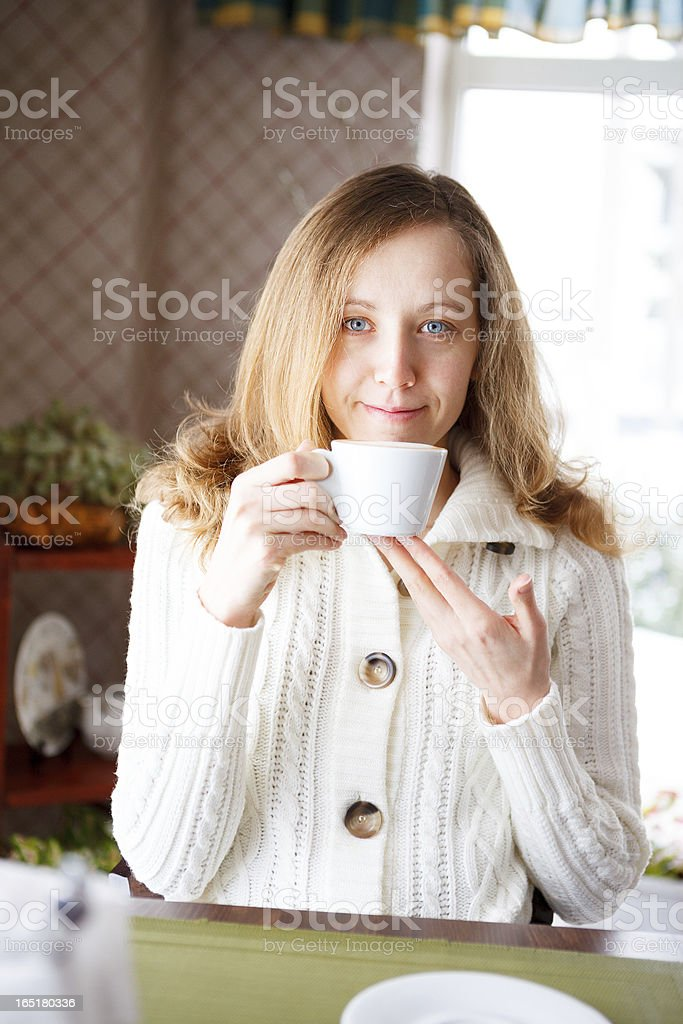 Smiling girl with a cup of coffee in hand royalty-free stock photo