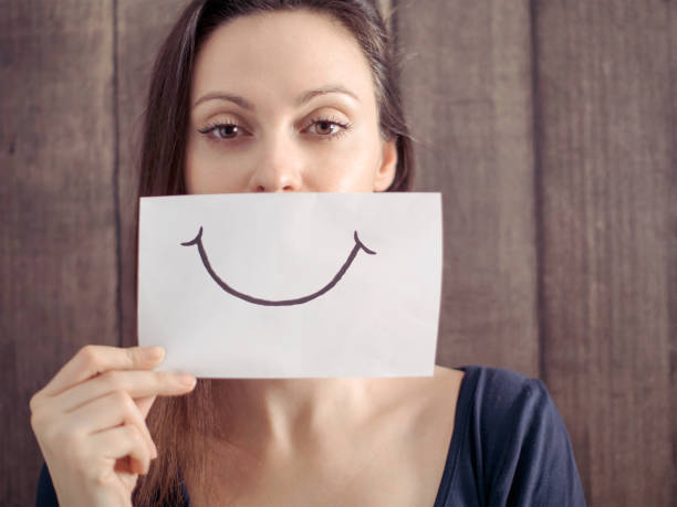 Smiling girl with a smile painted on paper stock photo